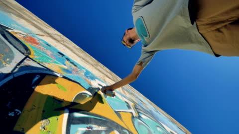 vídeos de stock e filmes b-roll de a ground level view on  a graffitist at work. - arte