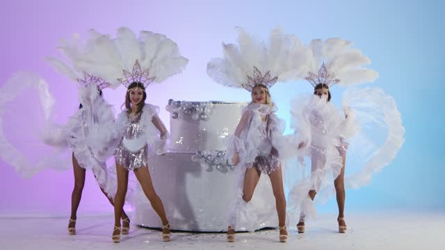 vídeos de stock e filmes b-roll de group adorable women in white snow queen costumes and feather headdresses are dancing near a large cake. dancers posing against a light blue studio background. new years greetings. slow motion - bolo rainha