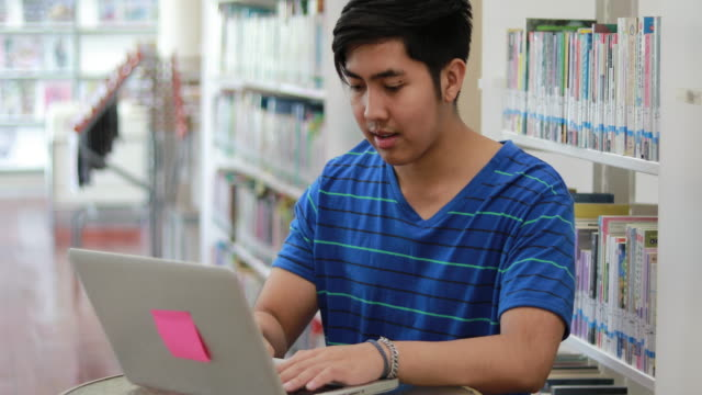 Group Asian Students Smile and reading book and using notebook for helps to share ideas in the work and project. And also review the book before the exam at library video
