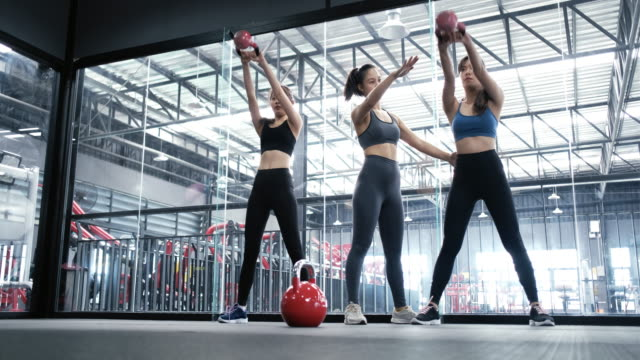 vídeos de stock e filmes b-roll de group asian women training exercise workout at fitness gym in sportswear with personal trainer coaching use kettlebells, sportive healthy bodybuilding, athlete builder muscles lifestyle concept. - gmail