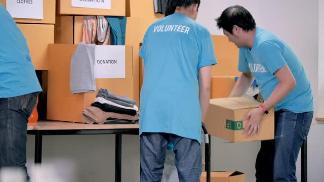 위기 코로나바이러스 covid-19에서 사람들을 위한 무료 음식과 옷 기부 를 준비하는 자원 봉사자의 그룹 아시아 청년 성인. 자원 봉사 - giving tuesday 스톡 비디오 및 b-롤 화면