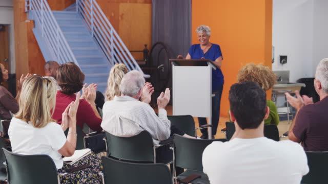 コミュニティセンターで表彰台に拍手を送る近所の会議に出席するグループ - community activism点の映像素材/bロール