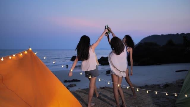 gruppe schöne frauen, die gemeinsam spaß haben im sommer bier trinken und camping, ferien und urlaub konzept. camping - freizeitaktivität im freien stock-videos und b-roll-filmmaterial