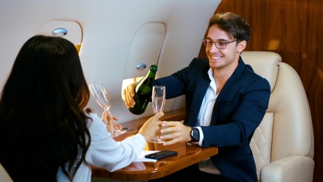 gruppen-geschäftsleute feiern mit einer flasche champagner und toasten ihren erfolg, während sie im privatjet fliegen. - billionär stock-videos und b-roll-filmmaterial