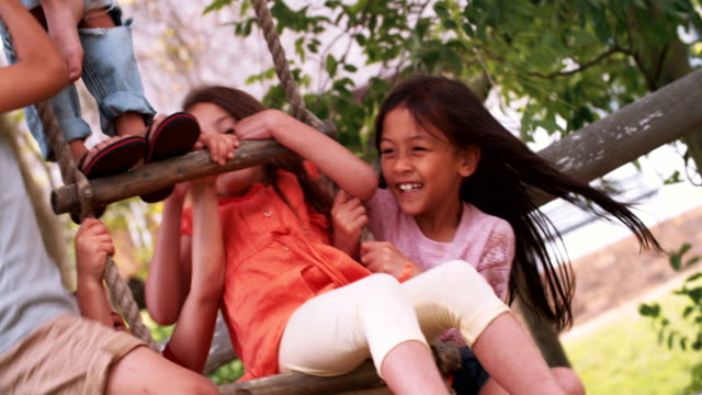Group children playing on the rope ladder of treehouse video
