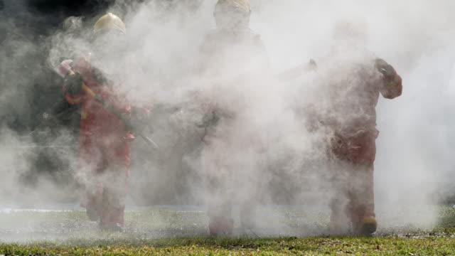 grupp brandman med uniform och hjälm promenader, blå krage arbetare - släcka bildbanksvideor och videomaterial från bakom kulisserna