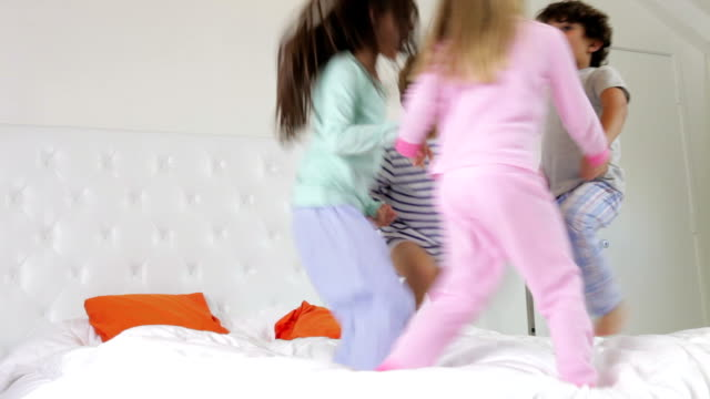 Group Four Children Playing Ring-Around-The-Rosy On Parents Bed video