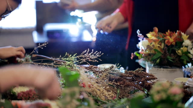 Group master florists, working with flowers, bouquets, boutonnieres, herbs, plants, decorations video