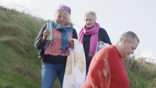 3人の女性のグループは、ビーチに向かう途中で岩の海岸沿いの道を歩いて泳ぐ。 - disruptagingcollection点の映像素材/bロール