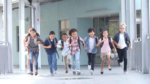 Grupo de 5 º grado escuela niños corriendo en un pasillo de la escuela - vídeo