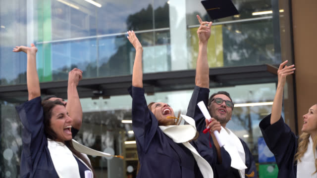 group of adult students throwing the graduation cap to the air celebrating they just graduated - tocco accademico video stock e b–roll
