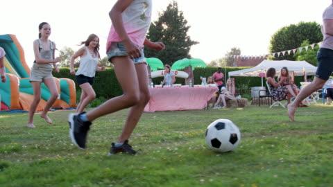 vidéos et rushes de groupe d'adultes et d'enfants ayant football match au jardin fete de l'été - tourné au ralenti - petites filles