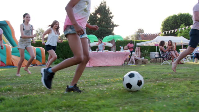 Group of adults and children having soccer match at summer garden fete - shot in slow motion Slow Motion Shot Of Children Playing Football Match With Adults At Summer Garden Fete match sport stock videos & royalty-free footage