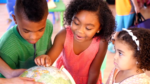 A group of African American children examine globe at daycare video