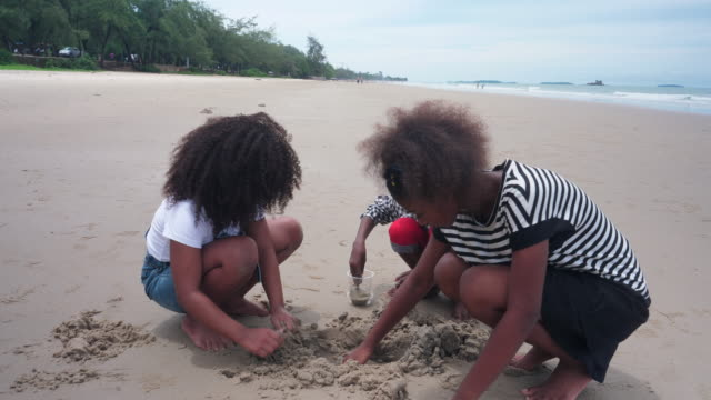 Group of African children playing in the sand on the beach