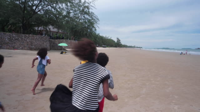 Group of African children running on the beach ; slow motion