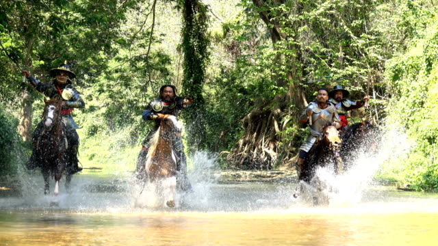 4K Group Of Ancient Warriors Riding Horse And Raise Sword Fighting With Enemy At Canal