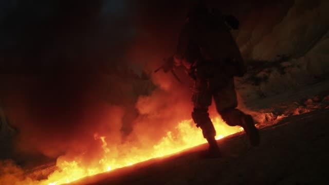 gruppe bewaffneter soldaten, die während der nächtlichen militäroperation durch das feuer laufen. zeitlupe. - konflikt stock-videos und b-roll-filmmaterial