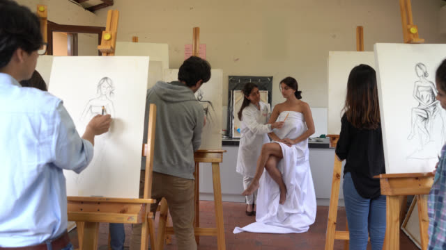 Group of art students drawing a model on canvas while teacher points out different aspects to detail video