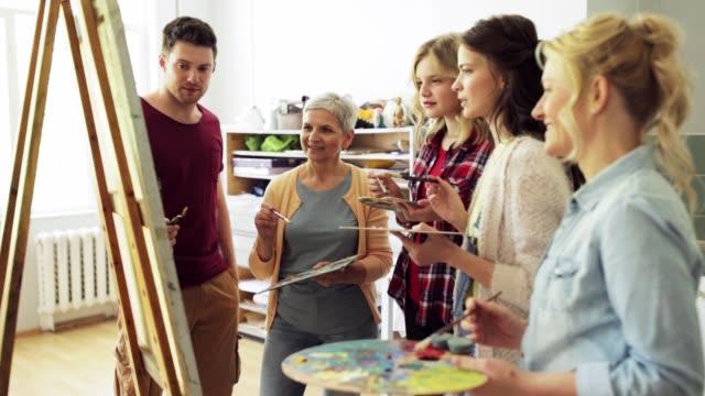 gruppe von künstlern diskutieren malerei an der kunstakademie - gemälde stock-videos und b-roll-filmmaterial