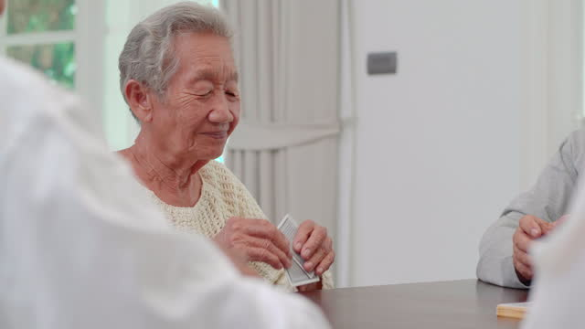 Group of asian active seniors age 60-70 yearold with group of happy old friends playing cards while talking spending a great time all together at nursing home.Social Seniors video