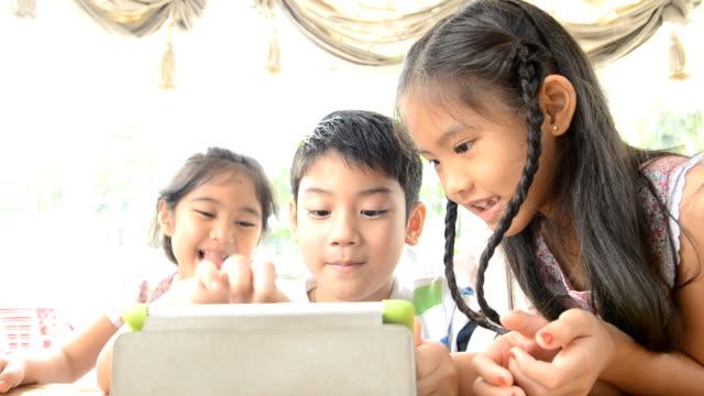 グループ、アジアの子供達が遊んで、タッチパッド ビデオ