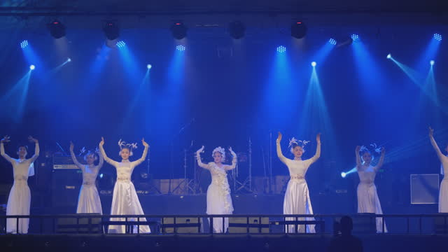 Group of Asian dancer with white and shiny dress show on stage with different colored disco lights