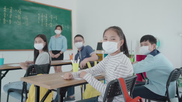 group of asian elementary school students and teacher wearing hygienic mask to prevent the outbreak of covid 19 in classroom while back to school reopen their school, new normal for education concept. - new normal video stock e b–roll