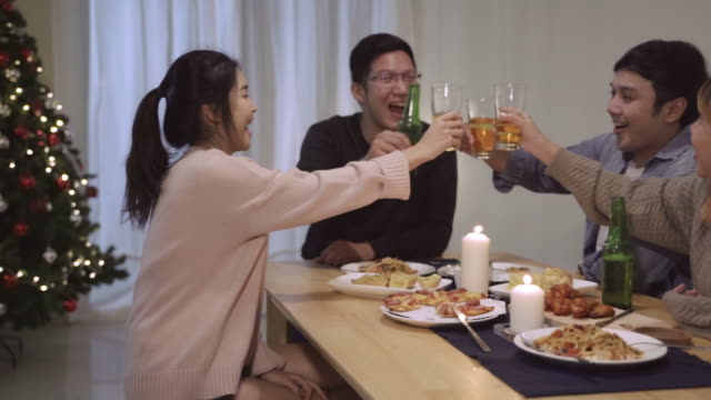 Group of Asian friends having fun cheer and talk in Christmas Dinner Party.Happy Thai people having fun together eating pizza during party at home.slow motion scene