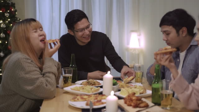 Group of Asian friends having fun talk in Christmas Dinner Party.Happy Thai people having fun together eating pizza during party at home.slow motion scene
