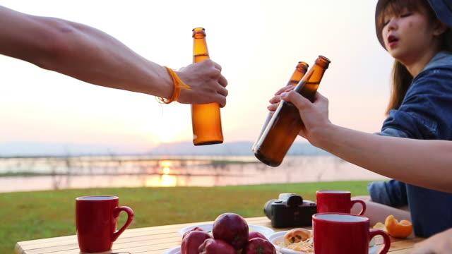 vídeos de stock, filmes e b-roll de um grupo de turista asiático dos amigos que bebe a cerveja alcoólica e que joga a guitarra junto com a felicidade no verão ao ter acampar perto do lago no por do sol - tea drinks