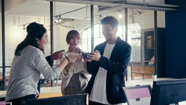 Group of Asian millennials watching and laughing on the video in office party (slow motion) Clips of modern open office space with millennials watching videos on the smart phone, taking selfies and celebrating. employee engagement stock videos & royalty-free footage