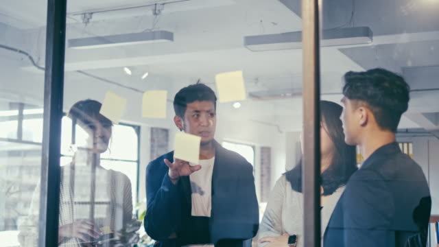 Group of asian office workers brainstorming with adhesive notes on the glass wall  (slow motion)