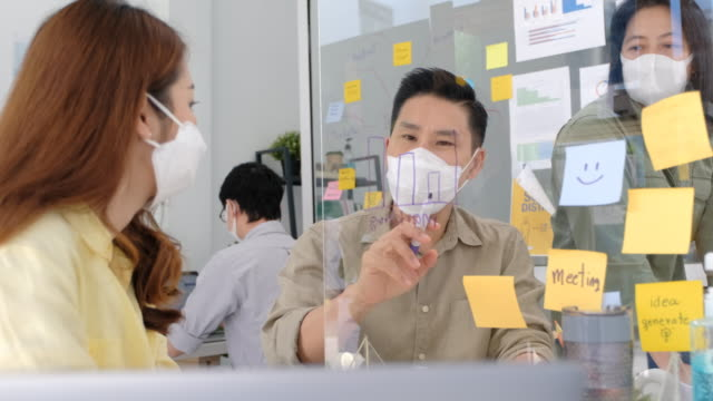 group of Asian officer casual meeting by writing on plexiglass at working desk in new normal office