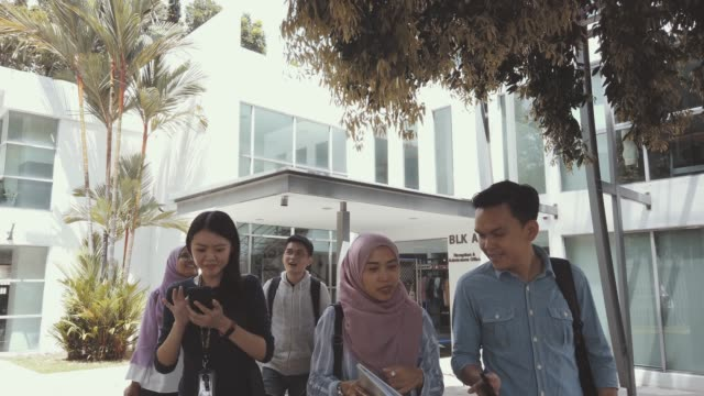 group of asian university student walking out from education building talking