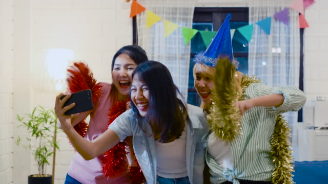 group of asian woman friend enjoy new year party and use mobile selfie while dancing in living room at home at night.celebration holiday festive concept - tajowie filmów i materiałów b-roll