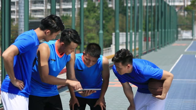 group of asian young adult basketball players discussing tactics video