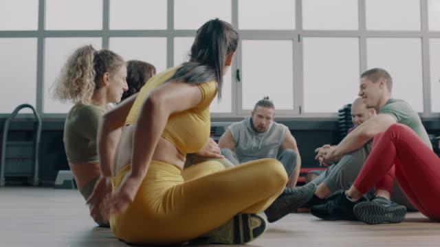 スポーツトレーニング後にジムでコミュニケーションを取る運動選手のグループ - ボディビル点の映像素材/bロール