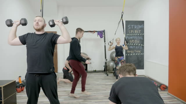 Group of athletic people team made from men and a woman training intensively at the gym by working out all groups of muscles video