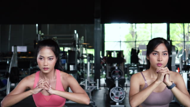 Group of athletic young Asian people in sportswear doing squat and exercising at the gym. Intense workout and healthy lifestyle concept