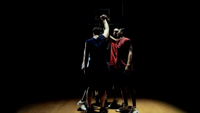 stockvideo's en b-roll-footage met groep van basketbal spelers huddling omhoog en rally juichen. - huddle