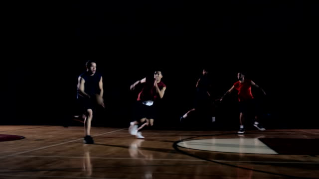 A group of basketball players playing ball on the court. video