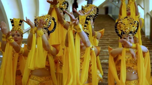 vídeos de stock, filmes e b-roll de grupo de mulheres asiáticas bonitas que estão e que dançam com mãos em uns vestidos e em chapéus amarelos tailandeses tradicionais - arte, cultura e espetáculo