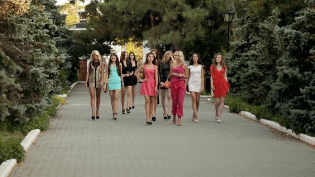 grupa piękne modele w jasny suknie spacery w parku - chudy filmów i materiałów b-roll