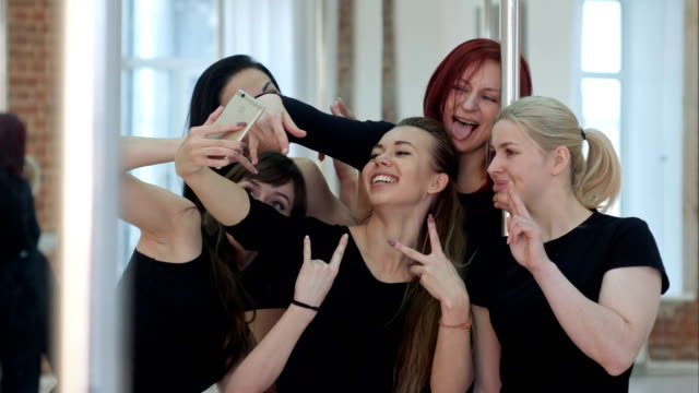 Group of beautiful young women taking a selfie after a pole dance class video