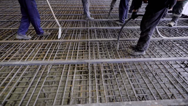 a group of builders poured concrete. the foundation of a large construction site, the builders are building a skyscraper or factory - quartiere generale video stock e b–roll