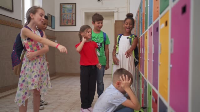 stockvideo's en b-roll-footage met groep pestkoppen die een schooljongen molesteren terwijl hij zijn gezicht behandelt terwijl het schreeuwen - lagere schoolleeftijd