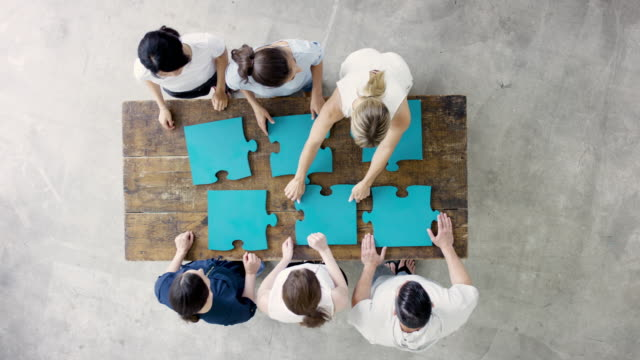 Group of Business Adults Sitting Around Table Putting Puzzle Together