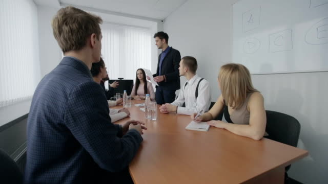 Group of business people appreciating businessperson at presentation. Slow motion video