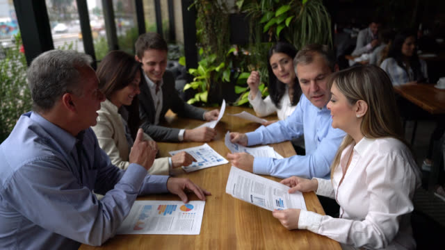 Group of business people discussing something while looking at documents at a restaurant Group of business people discussing something while looking at documents at a restaurant all very focused coworking stock videos & royalty-free footage
